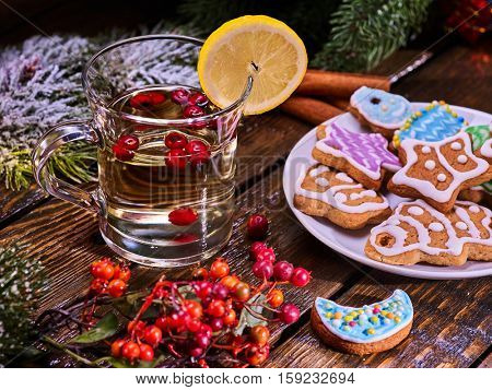 Christmas glass mug and Christmas multicolored cookies on plate with fir branches. Mag decoration lemon slice on wooden table. Christmas treats.