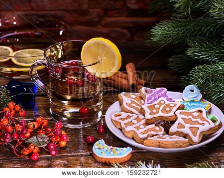Christmas treats. Christmas glass latte mug and Christmas multicolored cookies on plate with fir branches. Mag decoration lemon slice on wooden table in restaurant and cinnamon sticks.