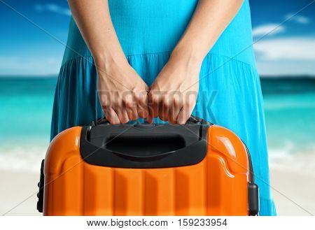 Woman In Blue Dress Holds Orange Suitcase In Hands On The Beach Background.