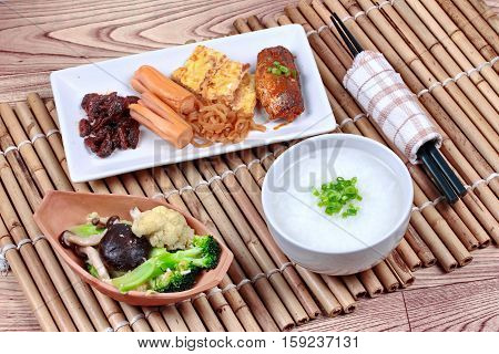 Rice gruel served with dish of sausage spicy clams ,sweet radish omelet and spicy caned mackerel and fried mixed vegetable.