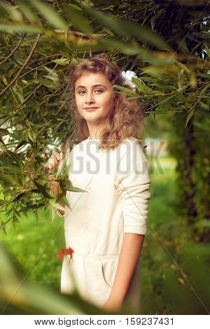 beautiful teenage girl 10 years old with long blonde hair stands in the summer with greenery and proudly looks at the camera fashionable posing