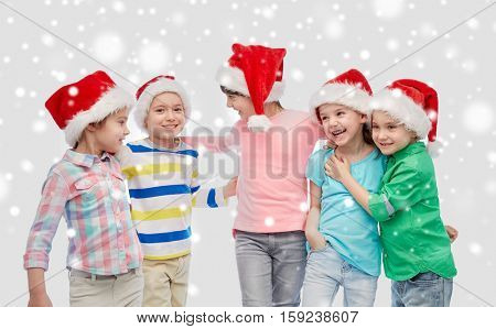 childhood, christmas, winter holidays, friendship and people concept - group of happy smiling little children in santa hats hugging over snow