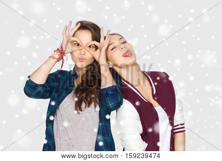 winter, christmas, people, teens and holidays concept - happy smiling pretty teenage girls or friends having fun and making faces over gray background and snow