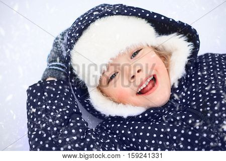 Small girl playing in snow. The concept of childhood and the winter season.