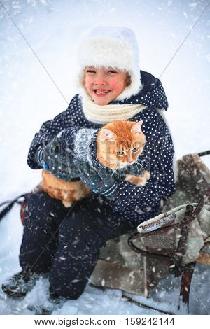 Little girl and a red cat on a sleigh ride in the countryside.