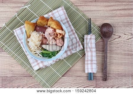 Thai noodle with pink tofu soup topped rugby fishball,wonton,porkball,boiled porkblood,pork rind,coriander and white mushroom call  Yen Ta Fo in Thai
