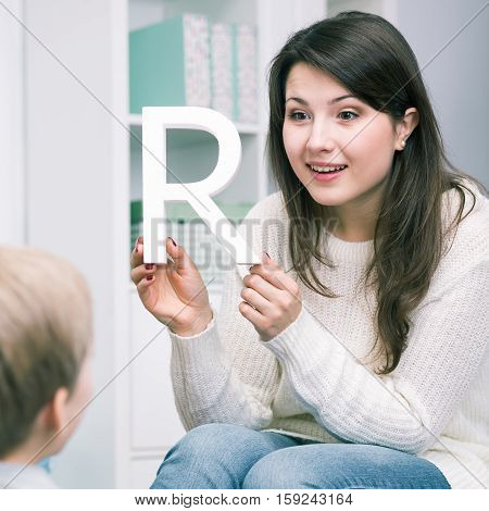 Speech therapist holding letter R and boy back view