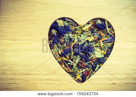 Dried herb leaves heart shaped on wooden surface. Herbaceous dry aromatic plant. Healing herbs herbal medicine concept.