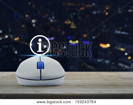 Wireless computer mouse with information sign icon on wooden table over blur light city tower