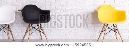 Brick Wall And Three Armchairs