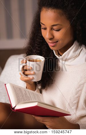 Woman Reading A Book And Holding A Mug