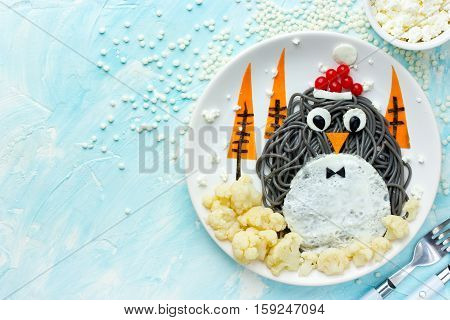 Fun food art idea for kids - penguin black spagehetti with fried egg and vegetables for Christmas or New Year festive dinner