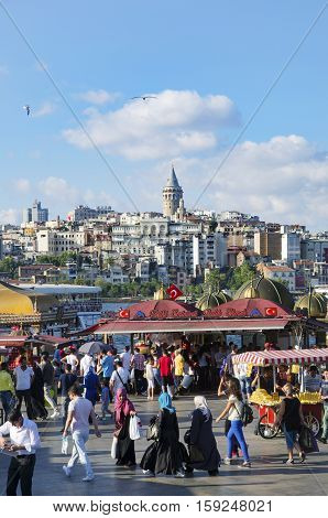 Istanbul Turkey - July 26 2016: Fish sandwich (Balik ekmek) at the Eminonu pier near the Galata Bridge. Background The Golden Horn is seen and the Galata Tower.