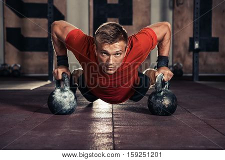 Handsome muscular man doing push ups on kettle ball in gym
