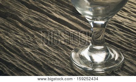 Stem of empty water goblet glassware on wooden board