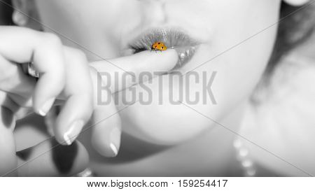 A woman kissing a ladybug on her finger