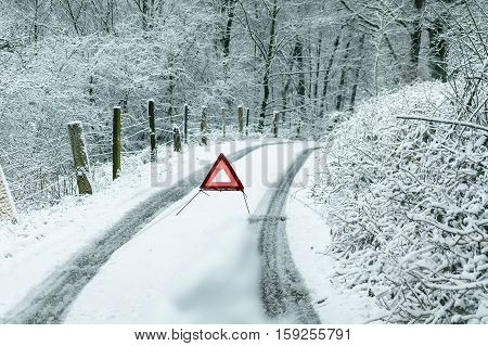 Rural road after heavy snowfall. In the middle of the road a warning triangle.