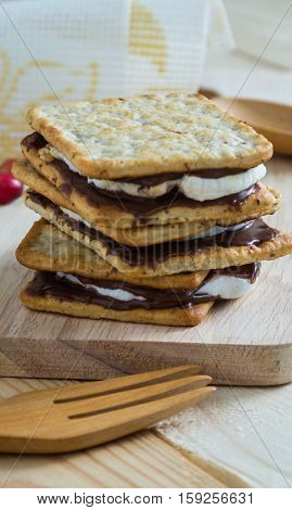 Smores placed on wooden block beside with wooden spoon