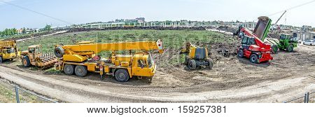 Panorama is showing the group of various machinery landscape transform. Yellow road roller with spikes crane cherry picker telescopic forklift and dumper truck are parked in front of building site.