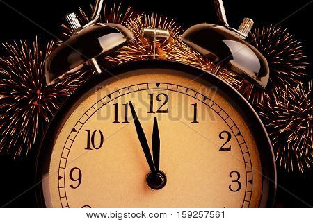 vintage alarm clock is showing midnight. It is twelve o'clock holiday happy new year festive concept on light glittering sparkle fireworks and black background