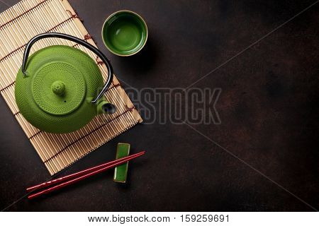 Green teapot and tea cup on stone table. Top view with copy space