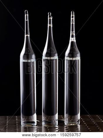Three Ampoules On Black Background