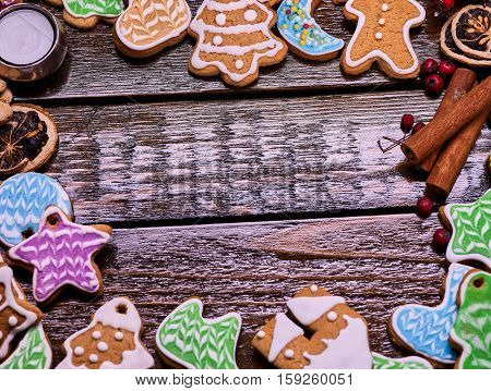 Christmas gingerbread cookies on woden table and candels. Frame with ginger snap and cinnamon sticks. Wooden place for text or wishes.