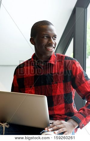 Portrait of happy young african man sitting outdoors with laptop and looking away