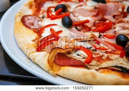 Pizza With Red Fresh Paprika And Black Olives On White Plate