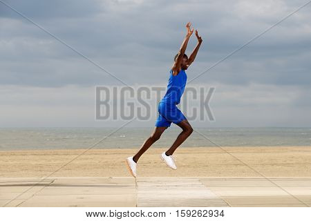 Fit Young African Man Jogging At Beach