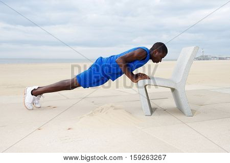 Healthy Young Man Doing Push Ups On Beach At The Beach