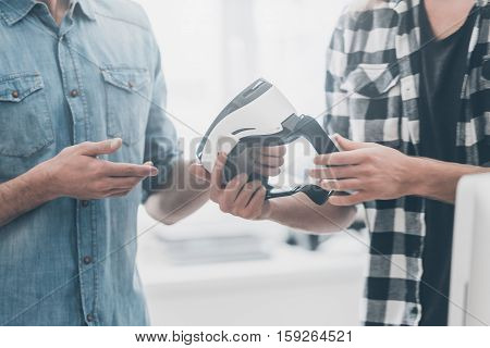 Try the new world of virtual reality! Close-up of two young businessmen in casual wear communicating while one of them gives VR headset to another