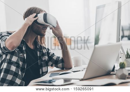 Another reality is here! Handsome young man with long hair adjusting his virtual reality headset while sitting at his desk in creative office
