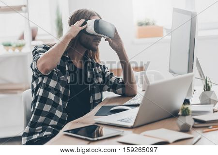 In my virtual world. Handsome young man with long hair adjusting his VR headset while sitting at his desk in creative office