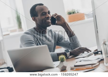 Talking on the phone. Handsome young African man talking on the mobile phone while sitting at his working place in office