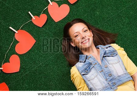 Woman lying down on the grass and thinking about love with heart shapes beside her.