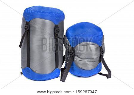 Tourist sleeping bags packed with varying degrees of compression isolated on white background. Studio shot.