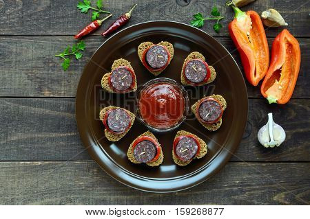 Sandwiches with black rye bread in the shape of a heart blood sausage (Morcillo) and pieces of sweet pepper on skewers in a ceramic bowl with tomato sauce on a dark wooden background. The top view.