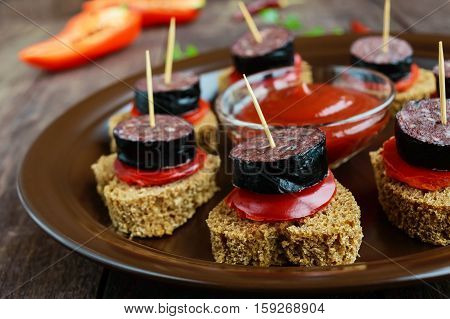 Sandwiches with black rye bread in the shape of a heart blood sausage (Morcillo) and pieces of sweet pepper on skewers in a ceramic bowl with tomato sauce on a dark wooden background. Close up