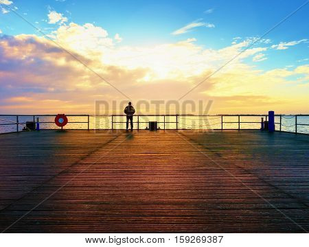 Man Hiker On Mole At Sea. Tourist On Wharf Looking Ower Sea To Horizon