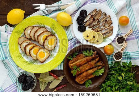 Fish dishes: White fish roll stuffed with eggs home made sprats fried capelin. The top view.