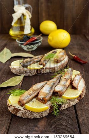 Sandwich with smoked fish capelin (sprats) lemon on black rye bread. Snack on a dark wooden table.
