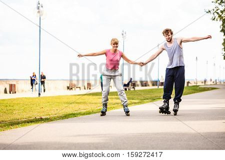 Active young people friends in training suit rollerskating outdoor. Woman and man couple holding hands riding enjoying sport.