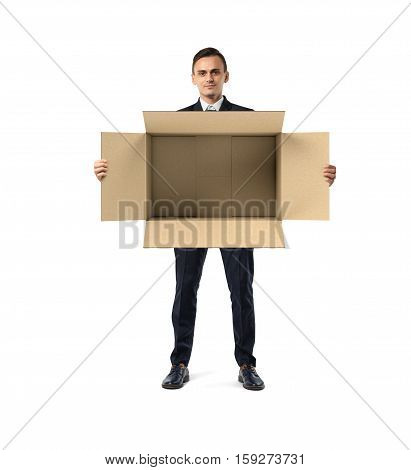 A businessman in a suit standing and holding a big open empty light beige cardboard mail box in his hands, isolated on the white background. Open to ideas. Packing and crating. Business development.