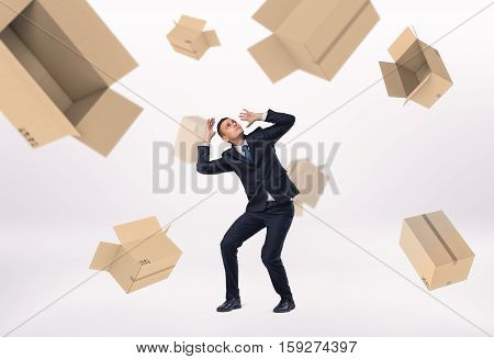 A frightened businessman and empty boxes falling on him, on the white background. Business loss. Crisis impact. Unsuccessful deal.