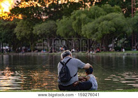 Grandpa And Nephew Relaxing In Chatuchak Park