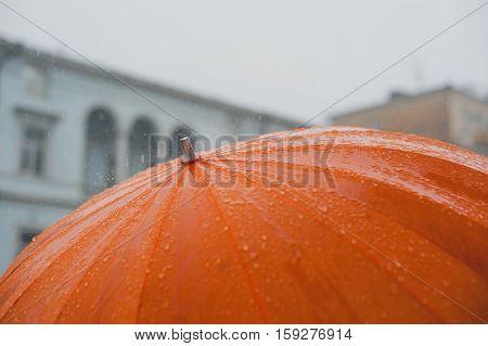 rain drops falling from a big orange umbrella