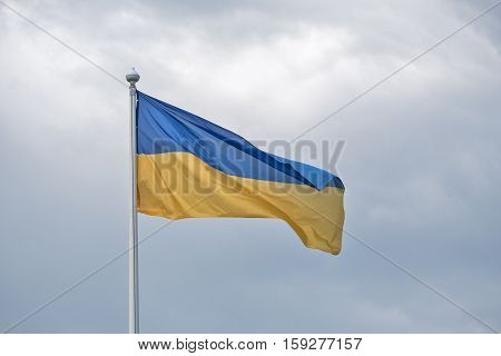 The flag of Ukraine flutters on wind against the background of gray clouds.