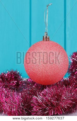 Pink Christmas ball and Christmas garland on blue wooden background