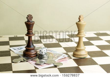 Chessmen money and dice on a chessboard